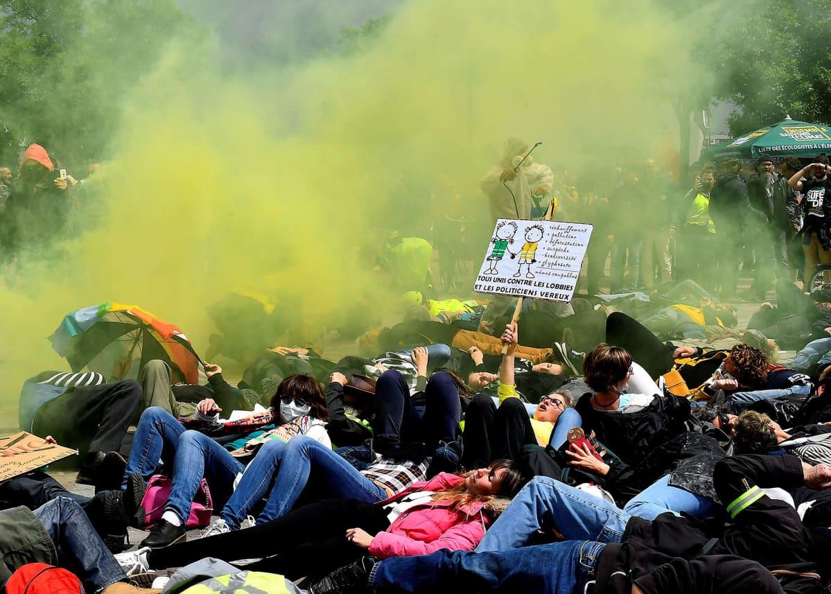 Keltaliivit ja ympäristöaktivistit protestoivat  Bayerin & Monsanto- yhtiötä vastaan 18. toukokuuta. Protestoijat makaavat maassa, keltaista väripuuteria leijuu ilmassa ja yksi protestoija esittää ruiskuttavasna kemikaalia maassa olevien päälle.