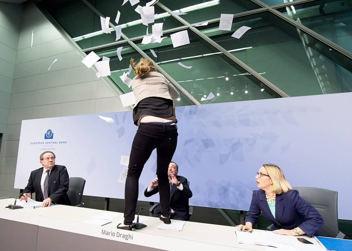 Mielenosoittaja hyppäsi Mario Draghin pöydälle ja heitti paperikasan ilmaan.