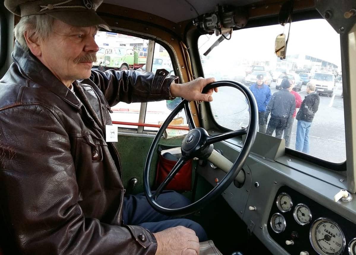 Mies vanhan kuorma-auton kuljettajan paikalla