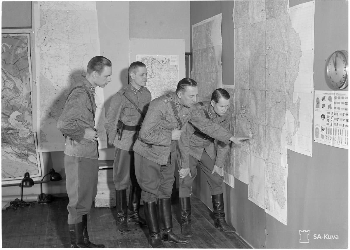 Reino Hallamaa osoittaa karttaa vanhassa sota-ajan valokuvassa.