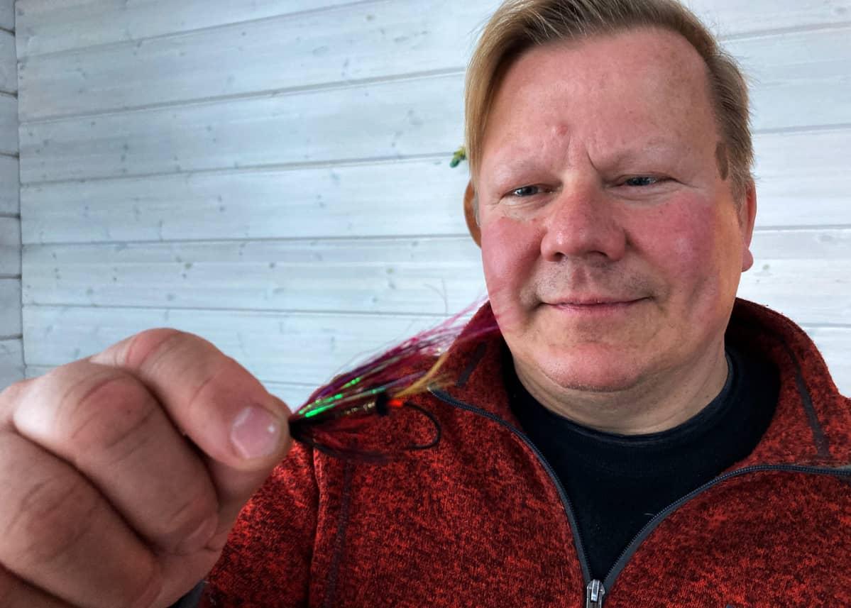 Punatakkinen mies pitää kädessään lohiperhoa.