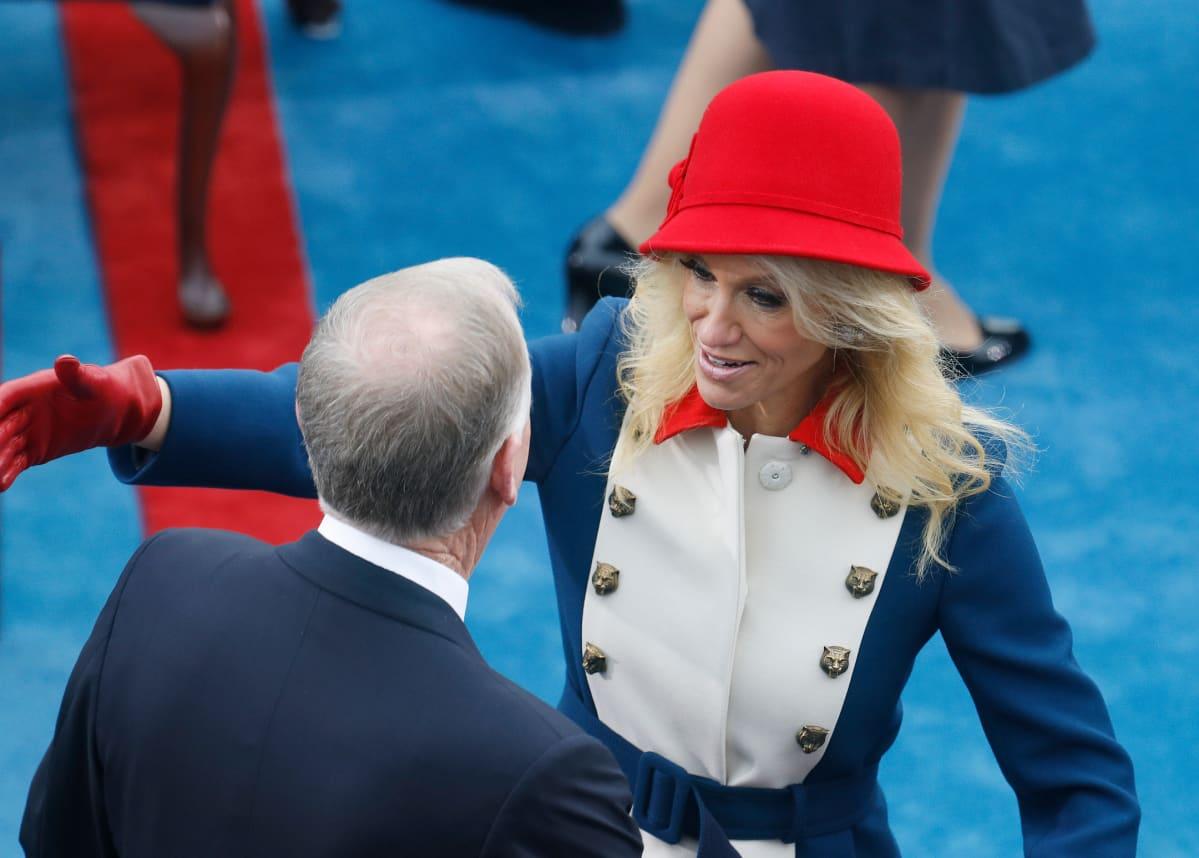 Sinipunavalkoiseen asuun pukeutunut Kellyanne Conway halaa entistä varapresidenttiä Dan Quaylea.