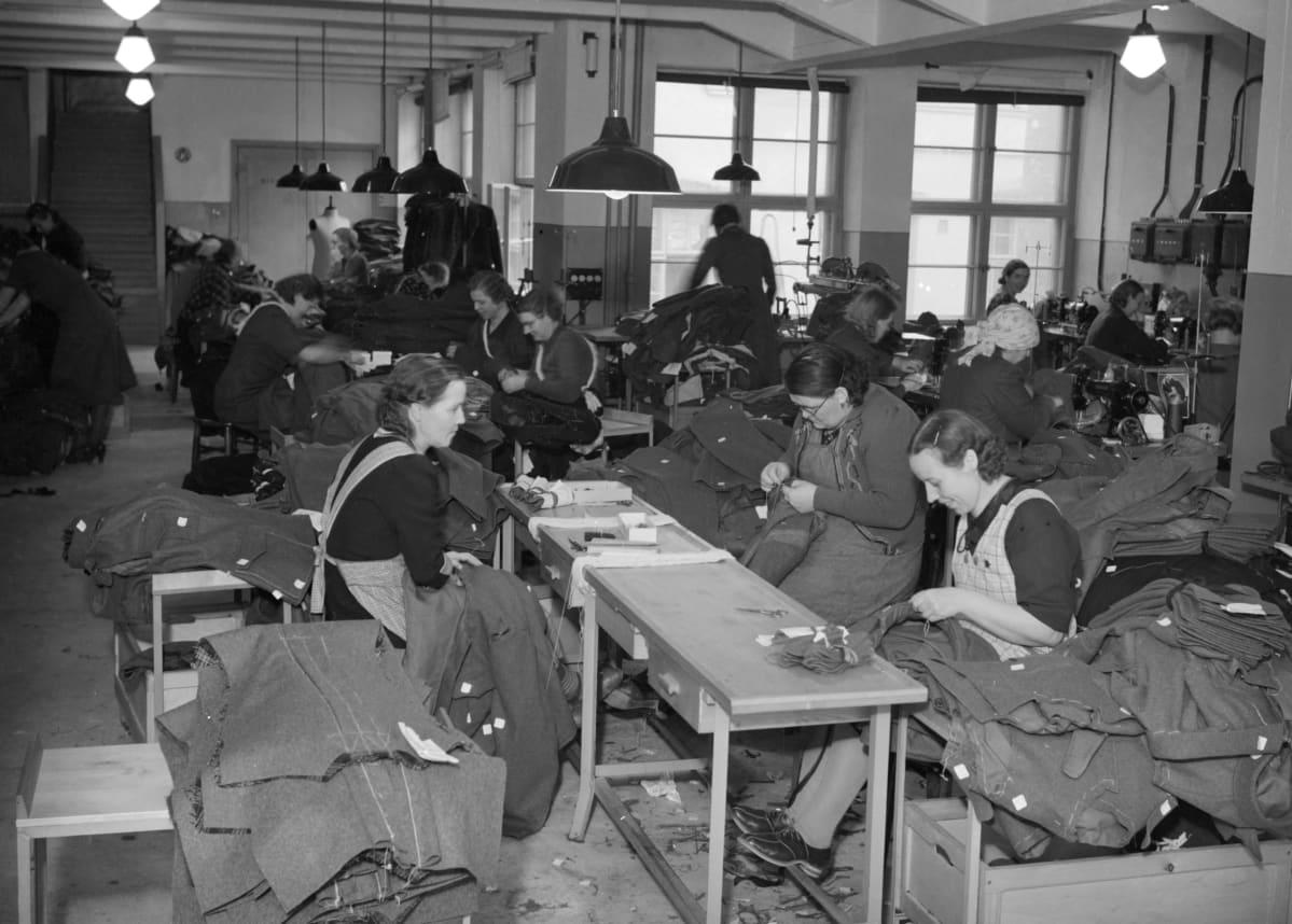 Joukko naisia istuu pöytien äärellä pukutehtaassa ja ompelee sotilasvarusteita.