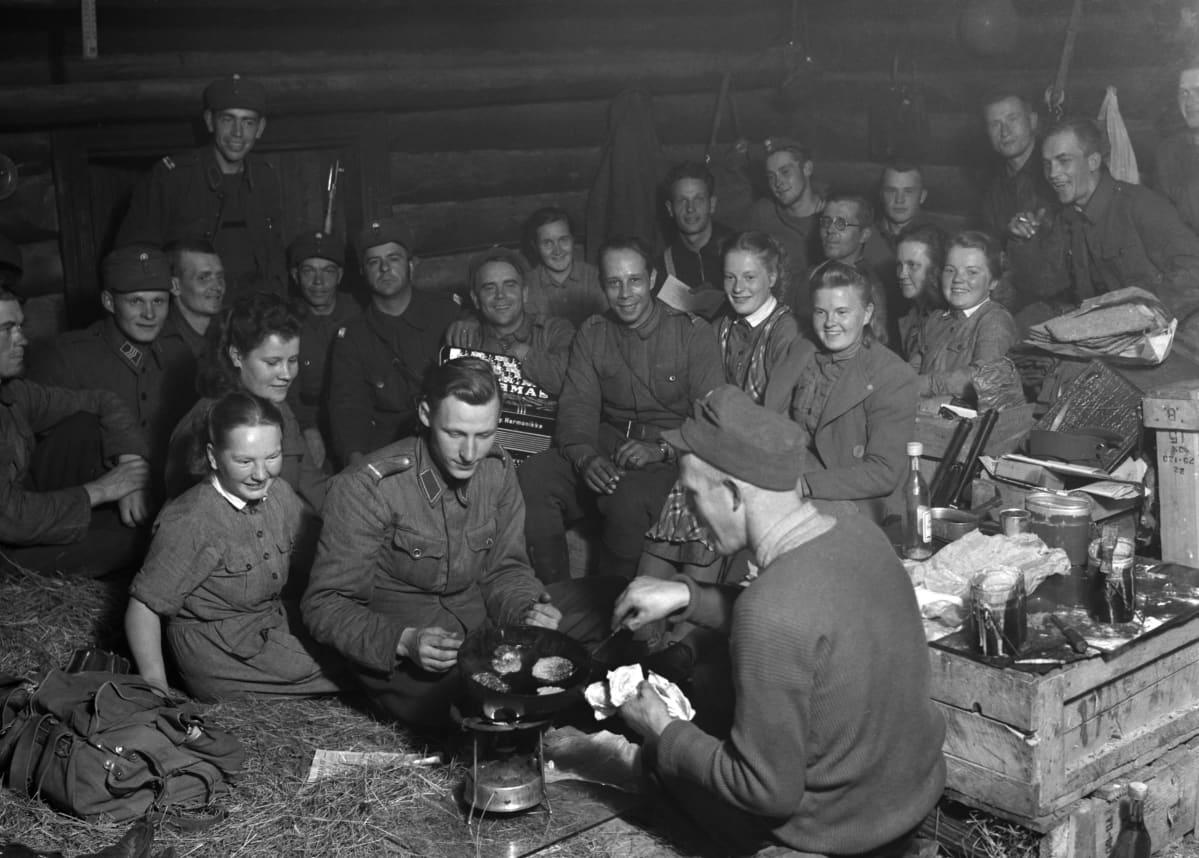 Sotilaat laittavat ruokaa pannulla korsussa. Taustalla muita sotilaita ja lottia, iloisia ilmeitä. Yhdellä sotilaalla harmonikka sylissä.