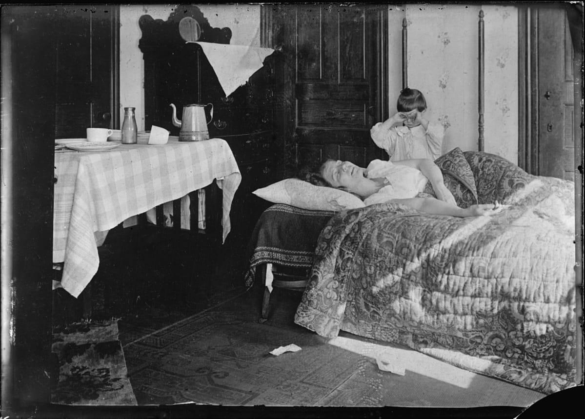 Mustavalkoinen valukuva  sängyssä makaavasta naisesta ja vuoreen ääressä itkevästä pikkutytöstä. Influenssan merkki on vain lattialle pudonnut nenäliina.