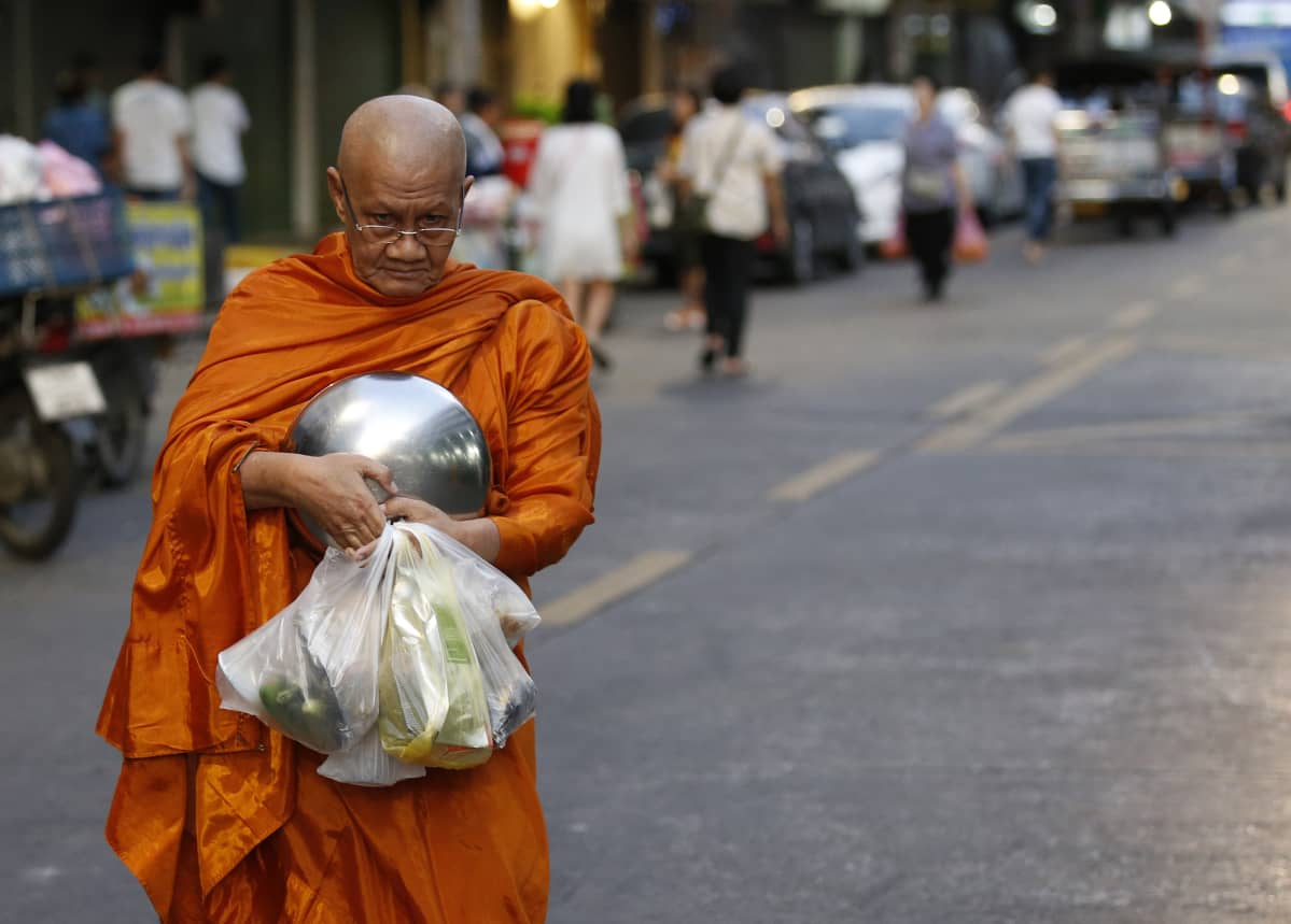 Buddhalaismunkki kantaa saamiaan ruokalahjoituksia.