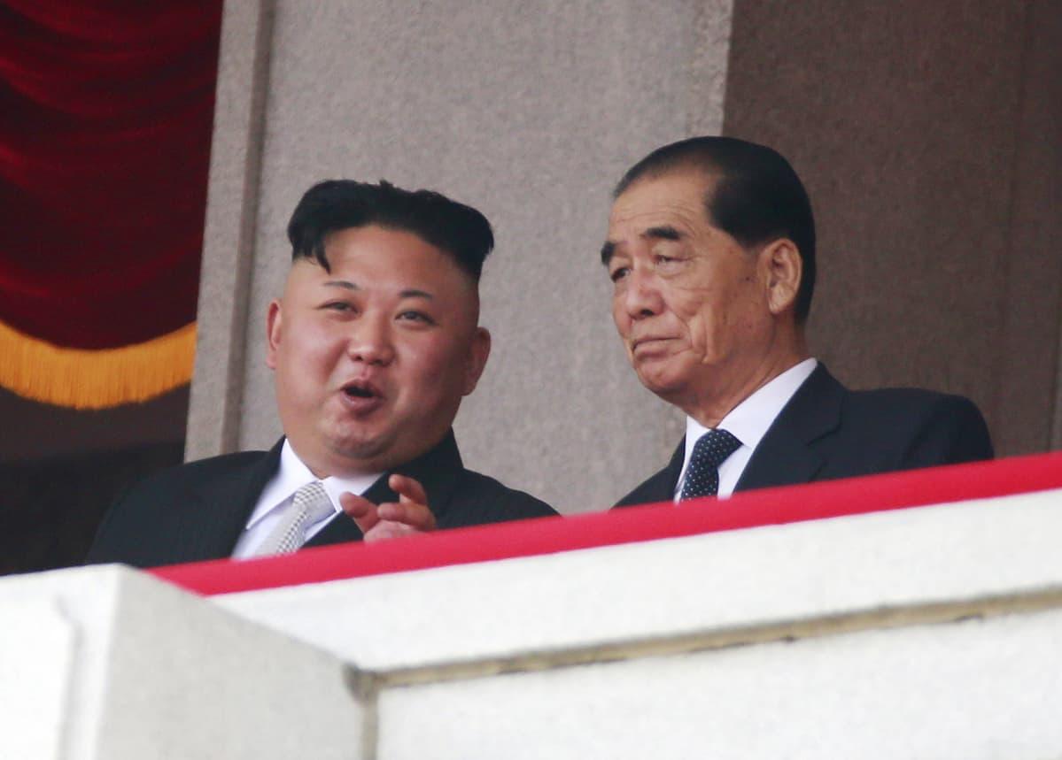 Pohjois-Korean johtaja Kim Jong-un (vas.) juttelee pääministeri Pak Pong-jun kanssa. He katselevat yhdessä paraatia, kun Pohjois-Korea juhli perustajansa Kim Il-sungin syntymän 105-vuotispäivää.