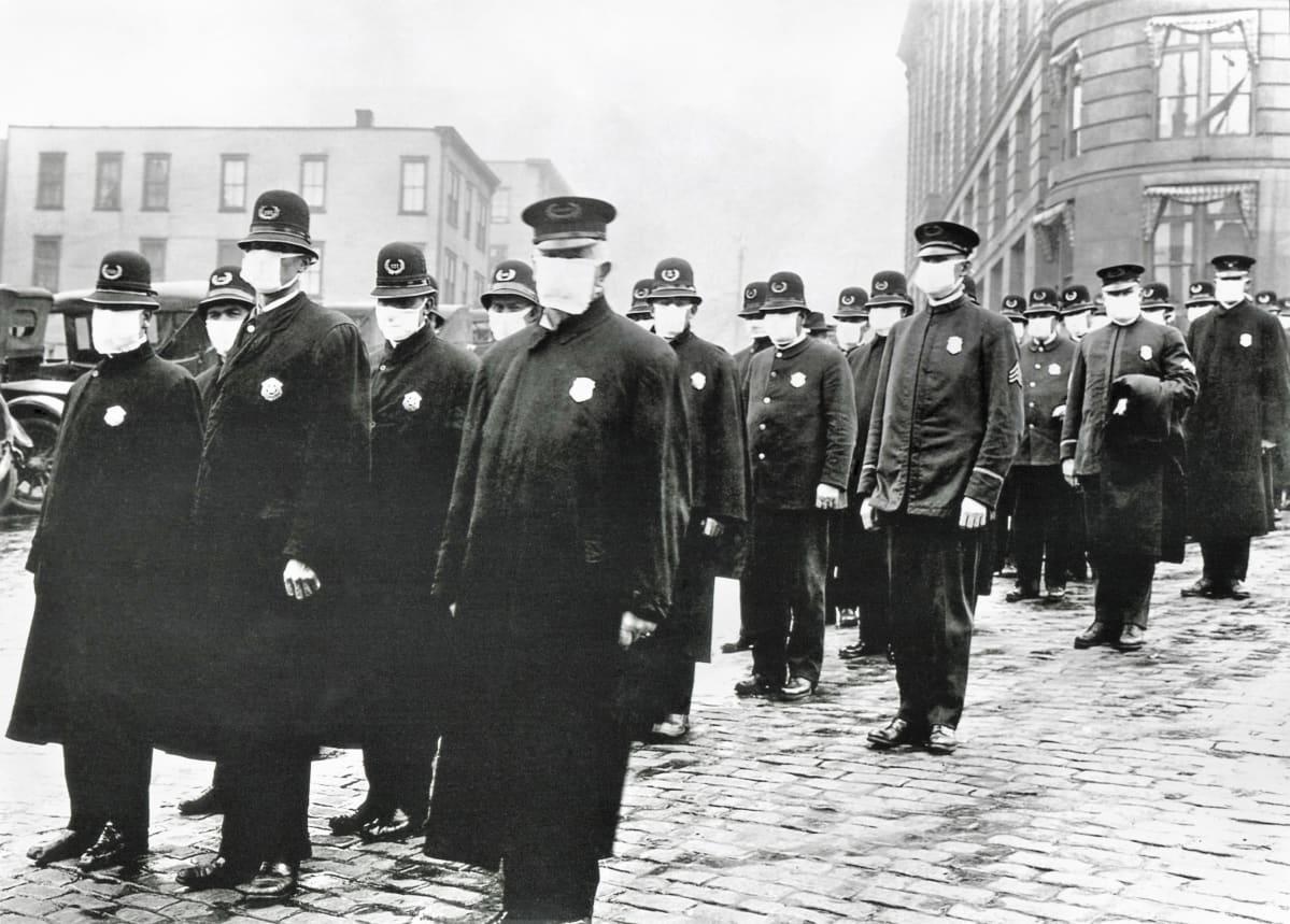 Joukko univormupukuisia poliisimiehiä seisoo kadulla suojaimet kasvoillaan. Kuva on mustavalkoinen.