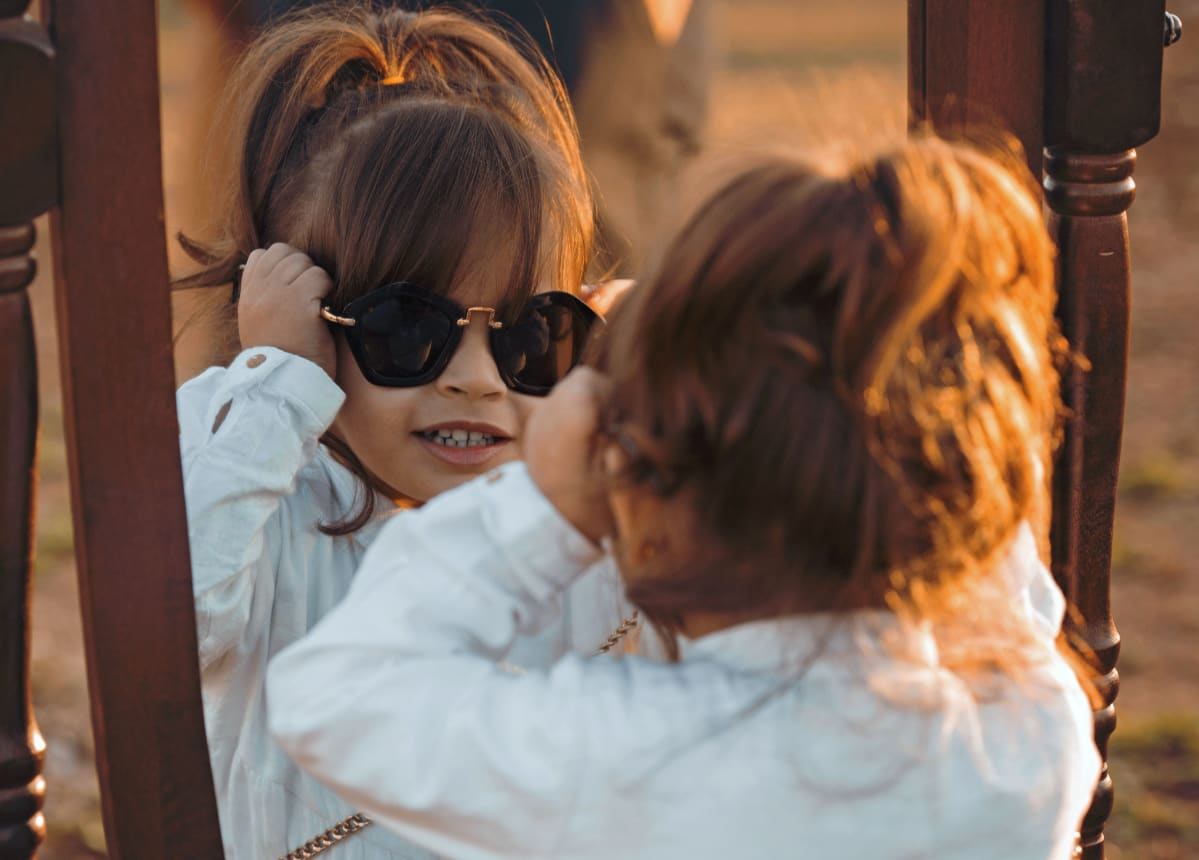 Pieni tyttö sovittelee aurinkolaseja peilin edessä.