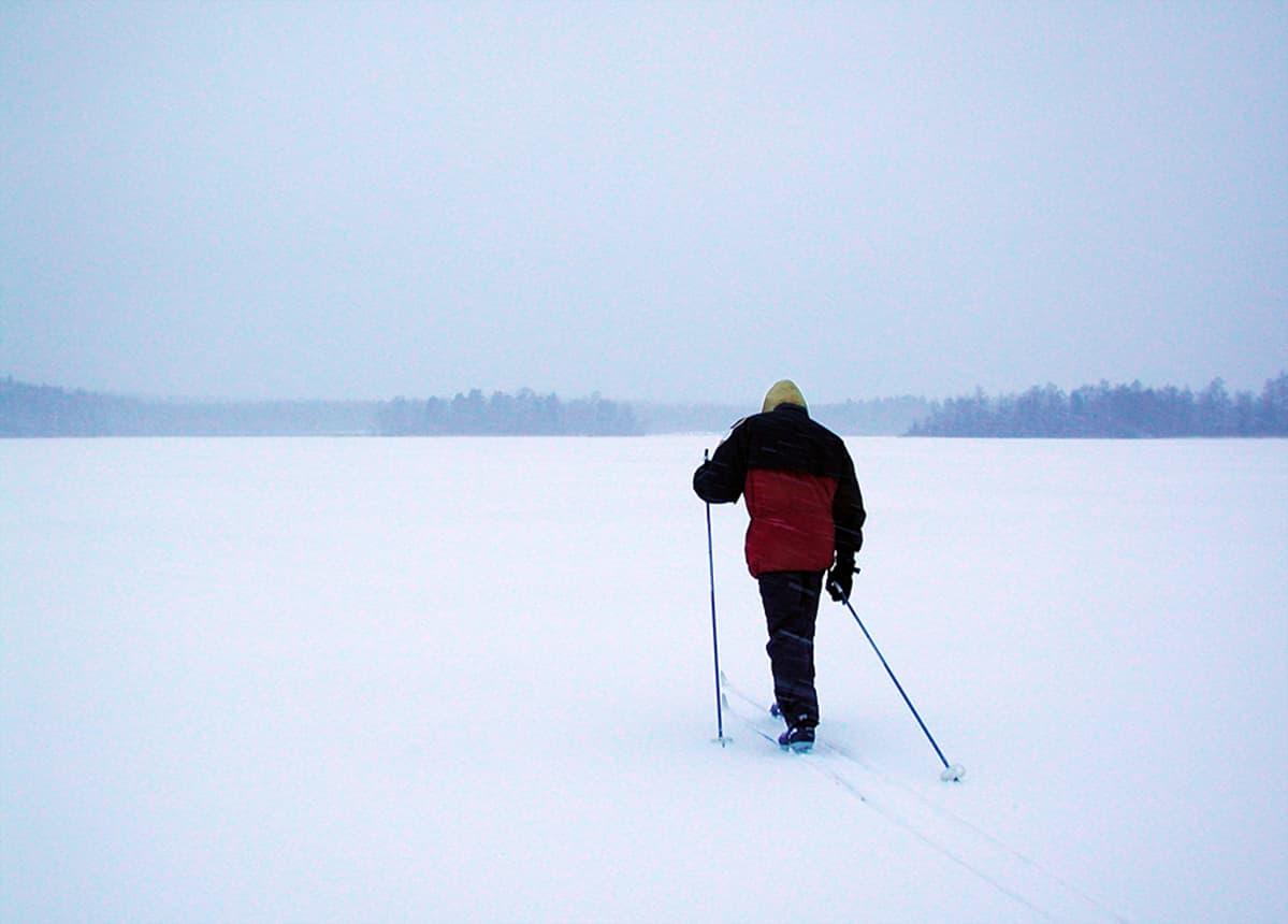 Mies hiihtämässä järvenjäällä.
