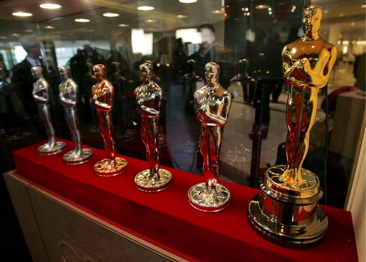 Kuusi Oscar-patsasta rivissä punaisella alustalla. Ensimmäinen on vasta ydin, viimeinen kullattu ja kiillotettu.