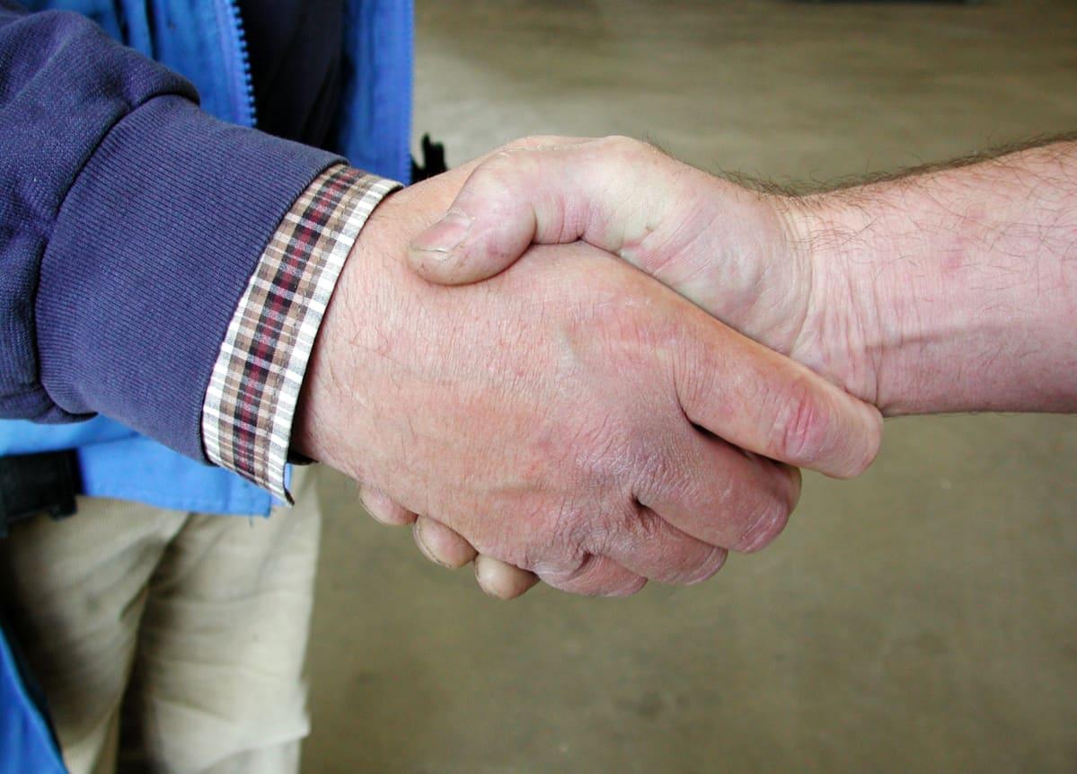 Kaksi miestä kättelevät, lähikuvassa kädet.
