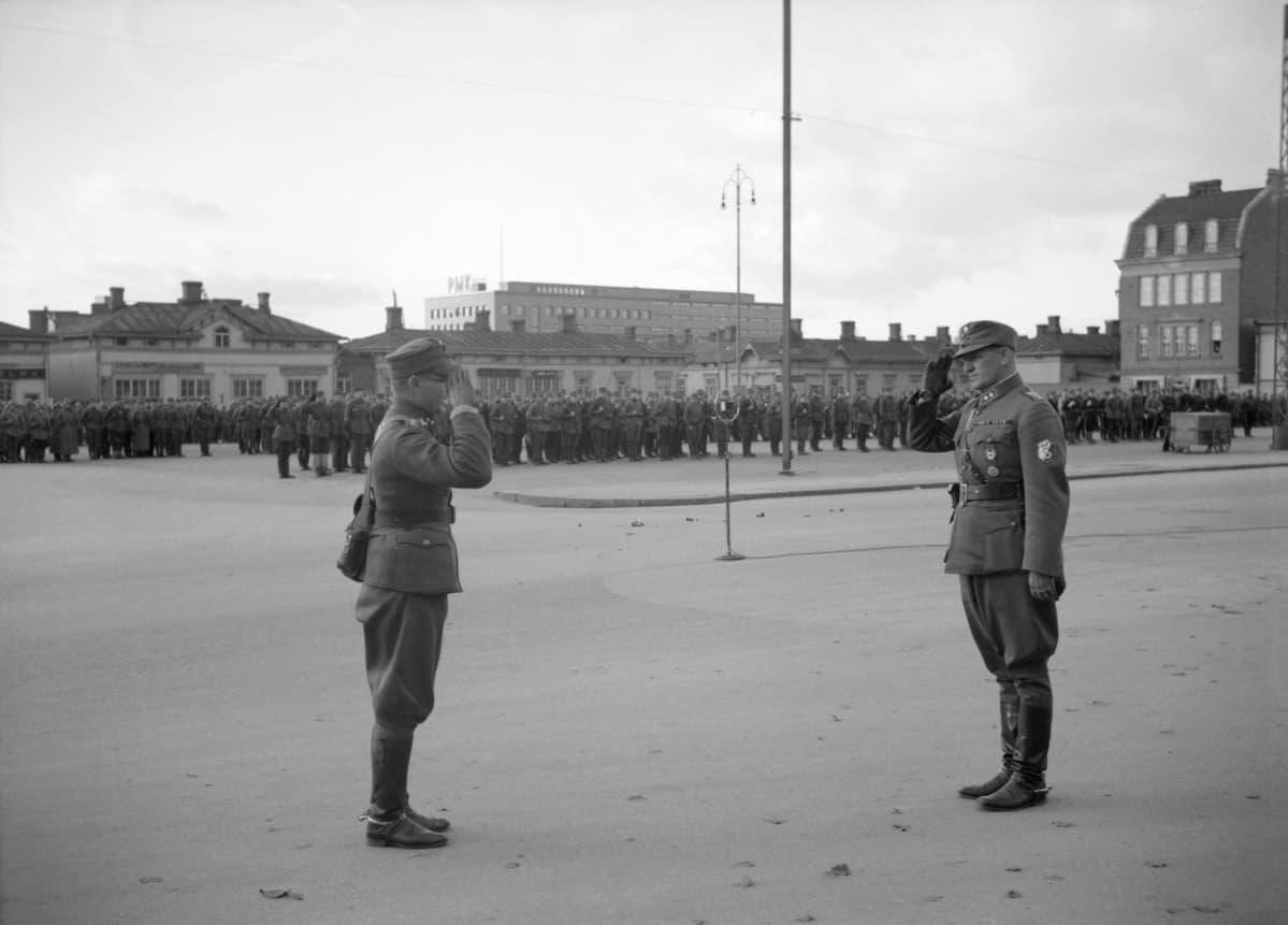 Etualalla kaksi upseeria, toinen tekee sotilatervehdyksen. Taustalla torilla sotaan lähteviä joukkoja rivissä.