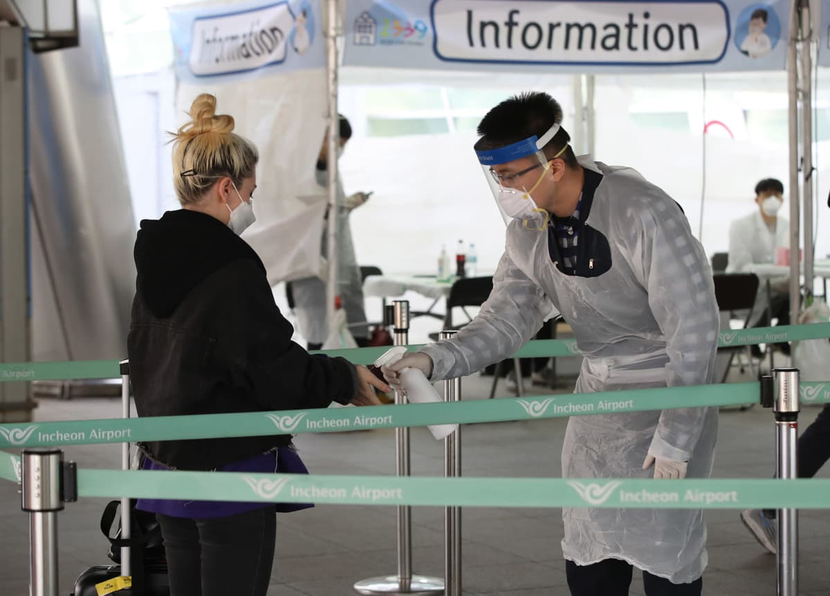 Suojavarusteisiin pukeutunut virkailija ottaa koronavirustestin eurooppalaislta matkailijalta lentokentällä Etelä-Koreassa.