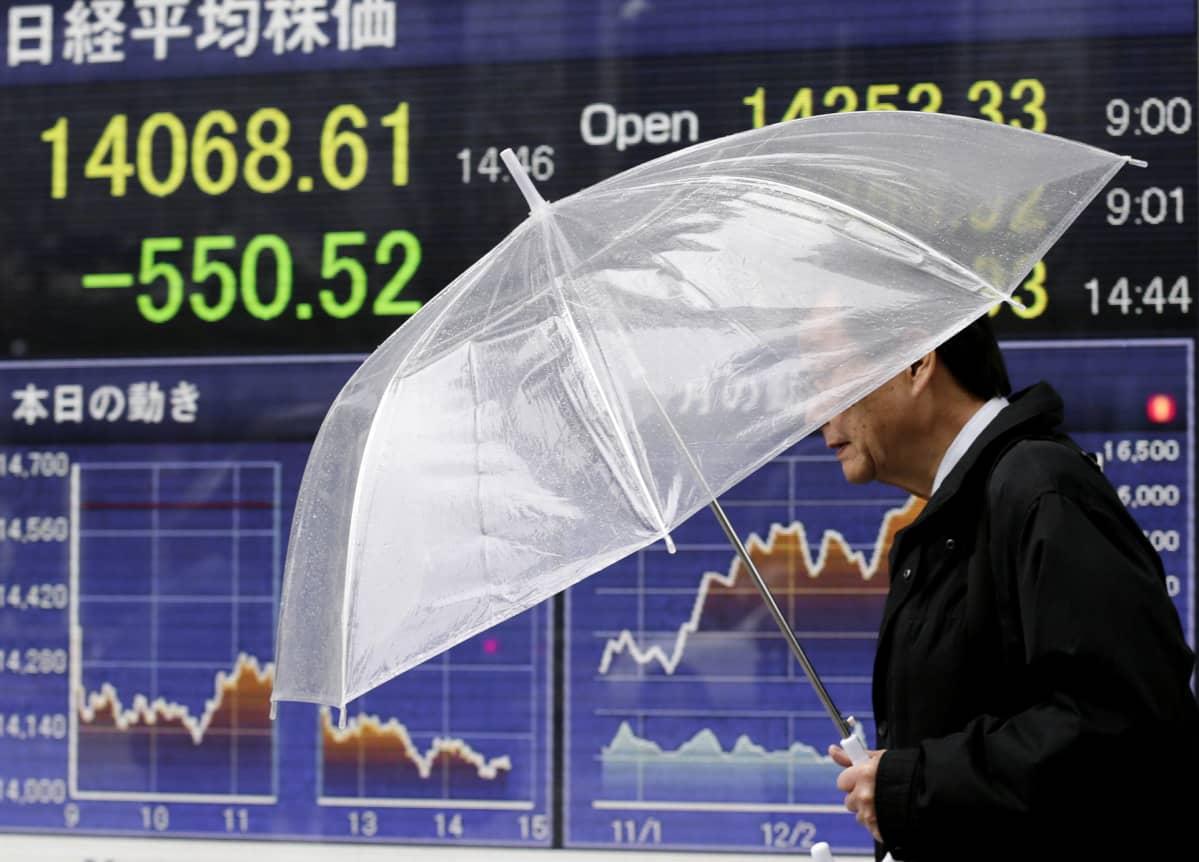 Mies kävelee sähköisellä näytöllä olevien pörssikurssien ohitse Tokiossa.