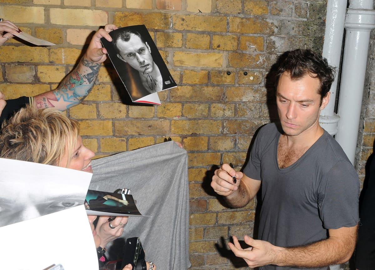 Fanit pyytävät nimikirjoituksia Jude Lawlta Lontoossa.