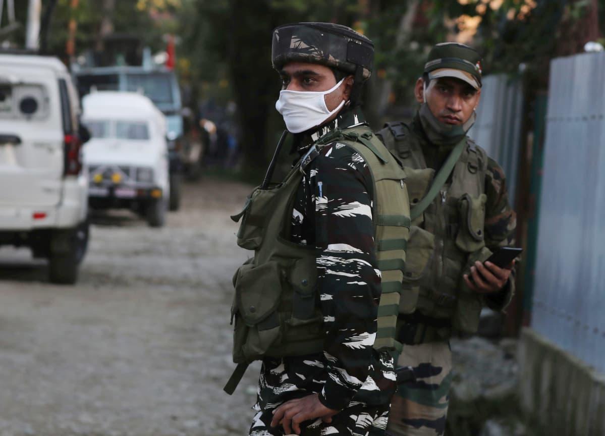 Kaksi aseistettua Intian turvallisuusjoukkoihin kuuluvaa miestä partioi kadulla Kashmirissa, toisella kasvomaski