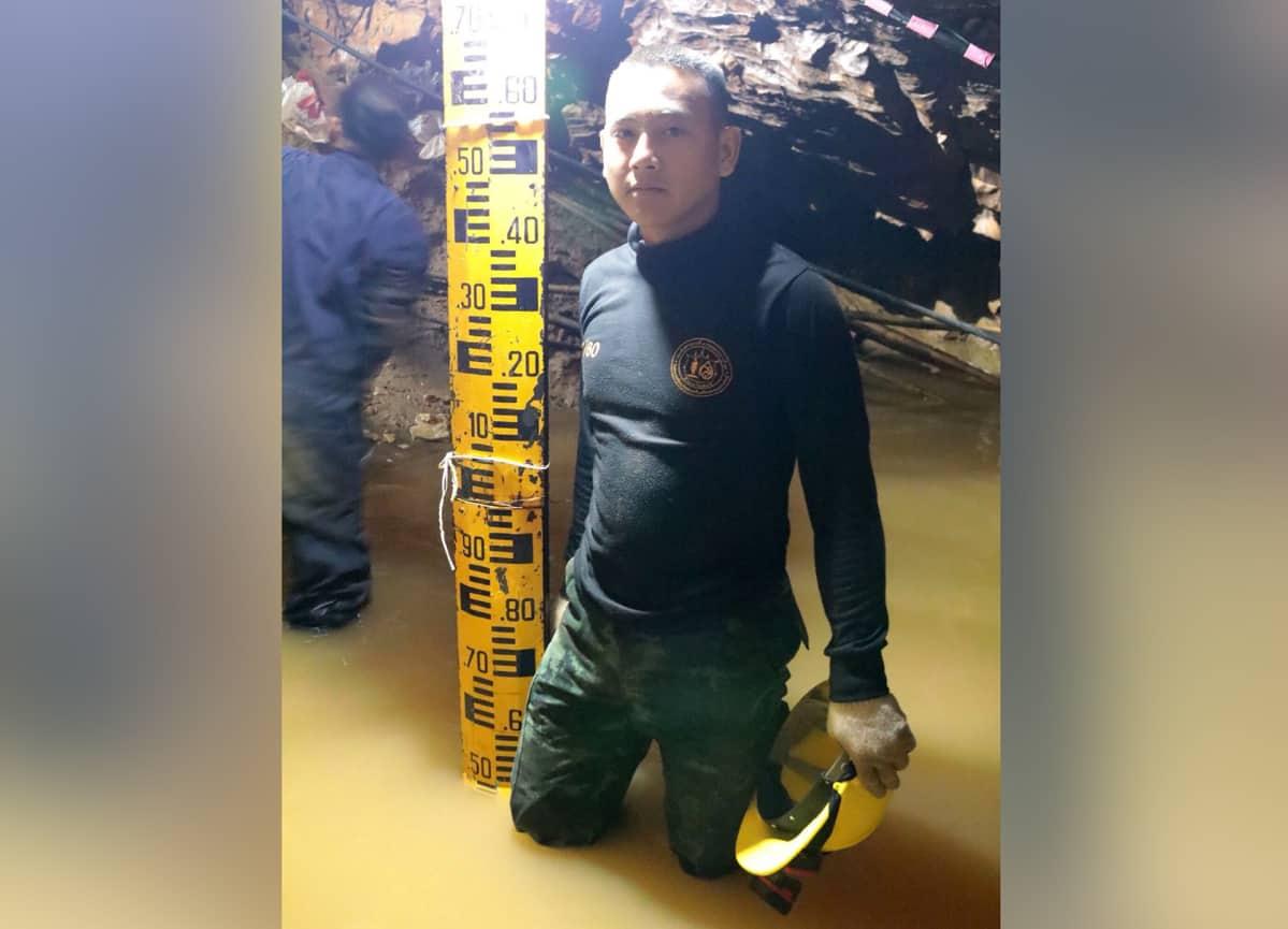 Pelastaja seisoo vedessä mittanauhan vieressä.