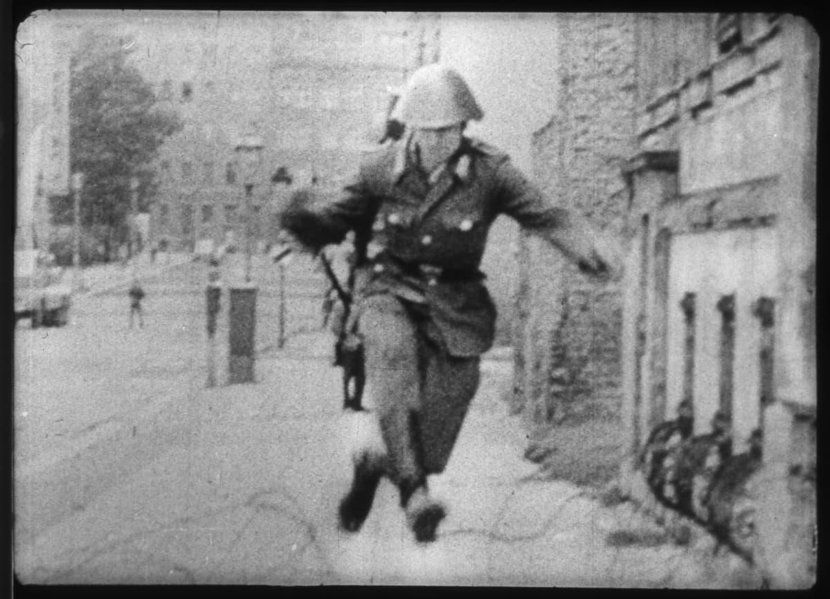 Itäsaksalainen poliisi hyppii piikkilankaesteen yli.