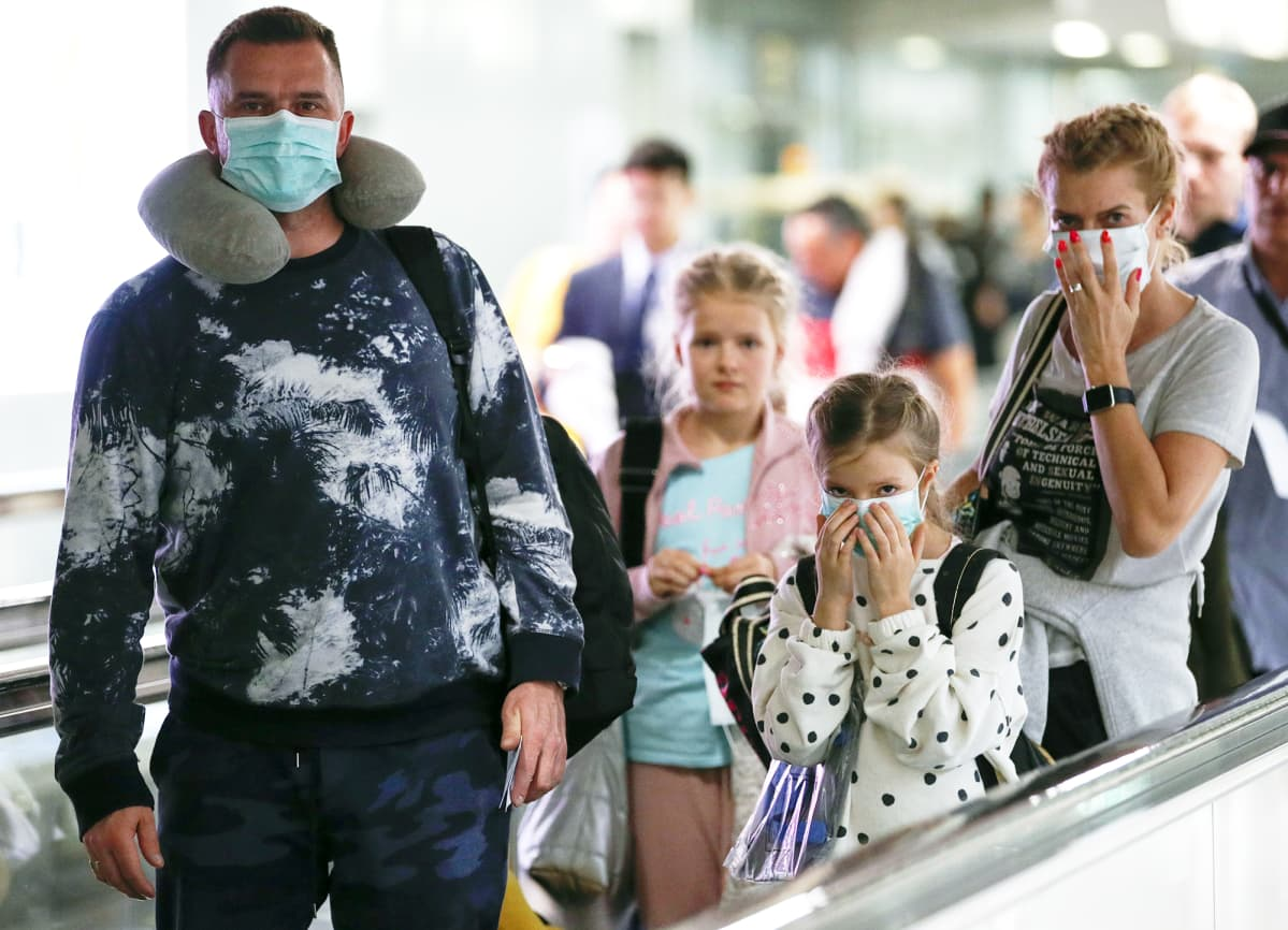 Hengityssuojaimiin pukeutunut perhe Suvarnabhumin lentoasemalla Thaimaassa.