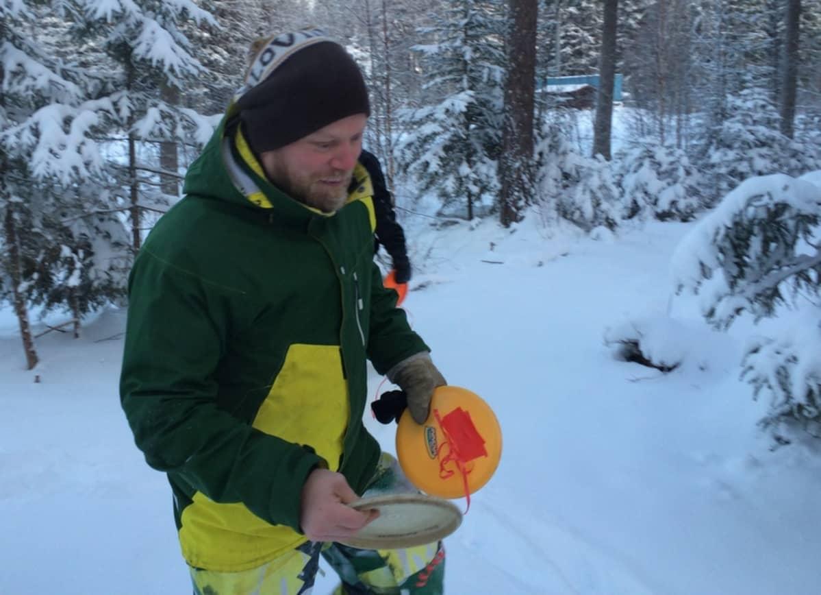 Mikko Pulkkinen ja frisbee talvisessa metsässä.