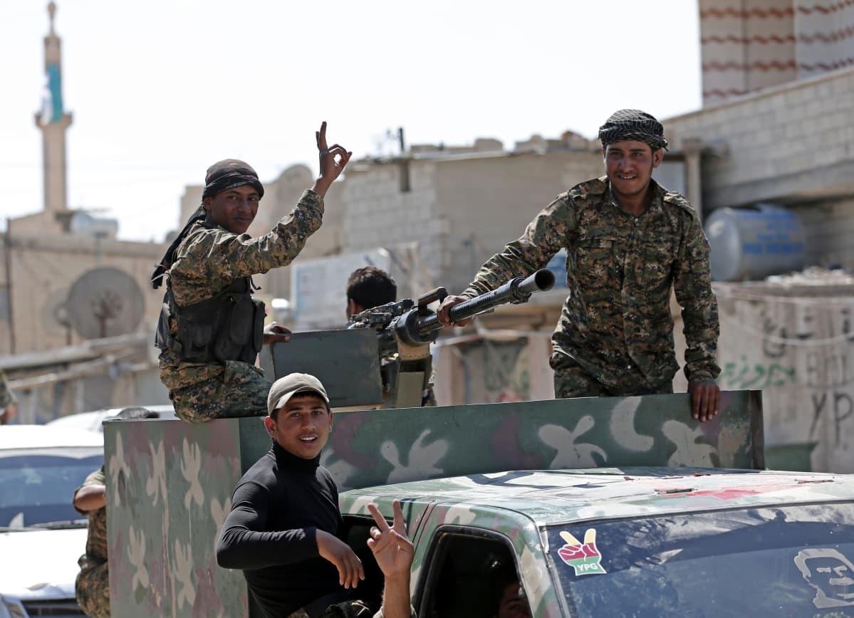 Kolme maastopukuihin pukeutunutta kurditaistelijaa pick-up-auton lavalla, jossa konekivääri. Yksi taistelijoista näyttää voitonmerkkiä.
