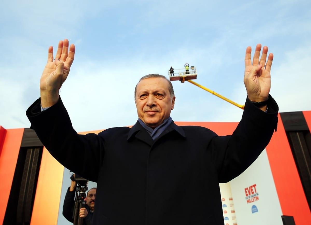 Presidentti on nostanut molemmat kätensä tervehdykseen.
