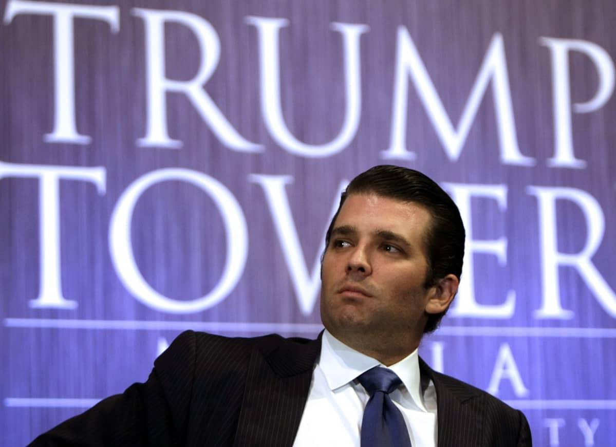Trump on tummassa puvussa, tumma kravatti kaulussaan istuvassa asennossa. Taustalla näkyy iso teksti Trump Tower sinisellä pohjalla.