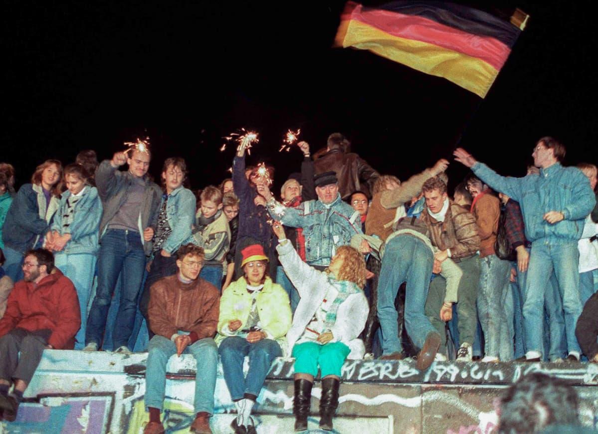 Berliiniläisiä juhlimassa rajan avaamista Berliinin muurin päällä 9. marraskuuta 1989.