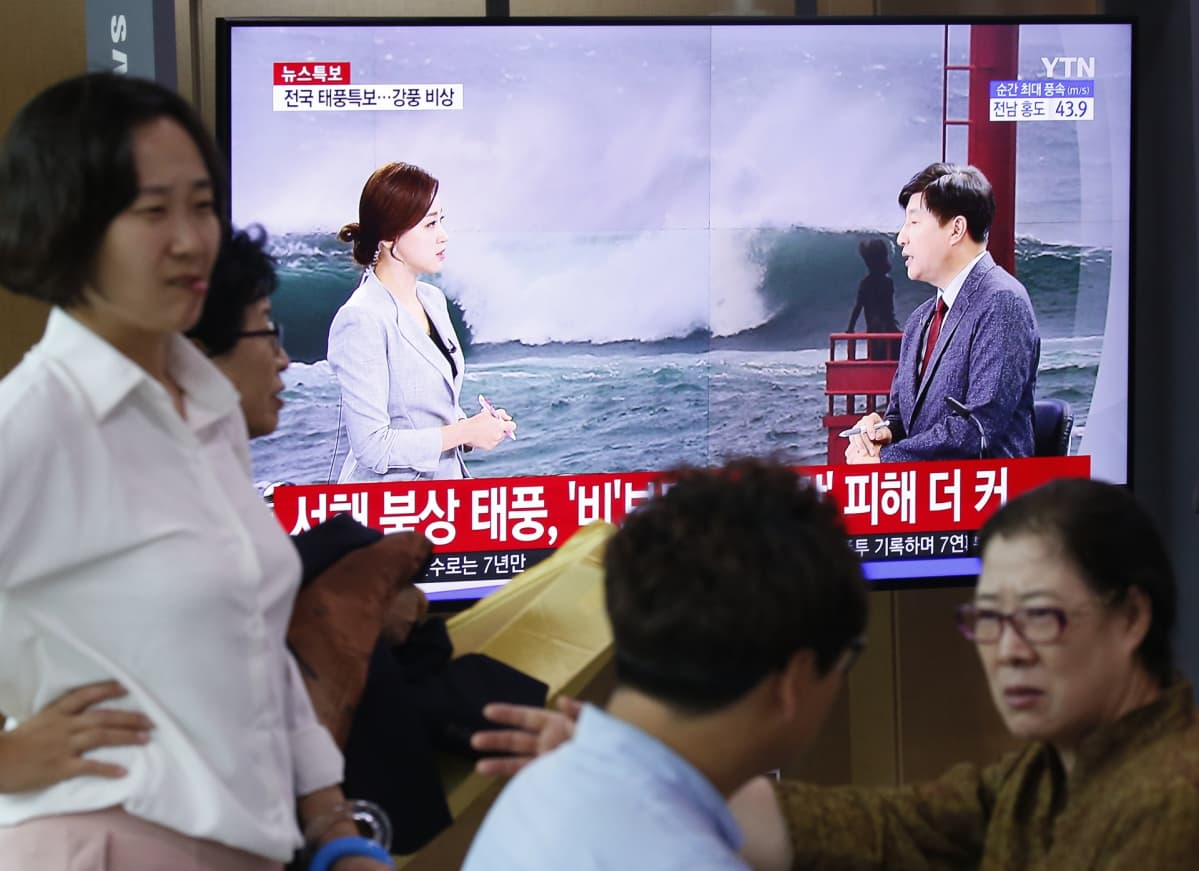 Myrskylähetys tv-ruudussa. TV:n edessä useita ihmisiä.