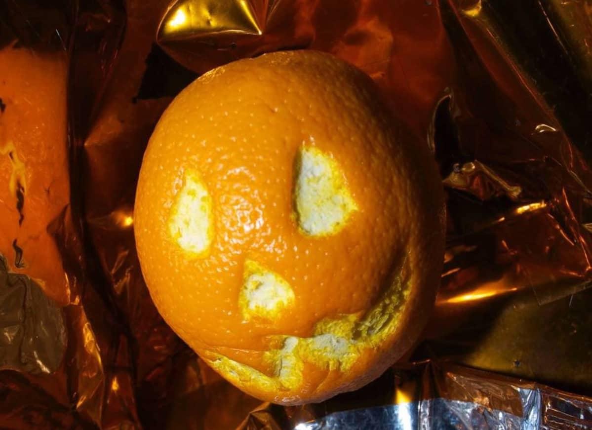 Appelsiini, johon on kaiverrettu irvistävät kasvot