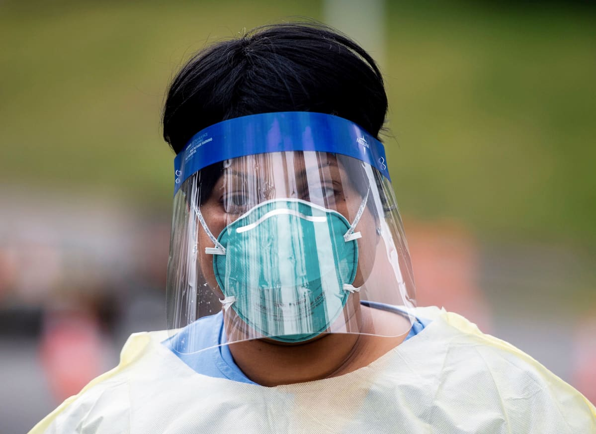 Hengitysuojaan ja suojapleksiin pukeutunut  hoitotyöntekijä Virginian Arlingtonissa.