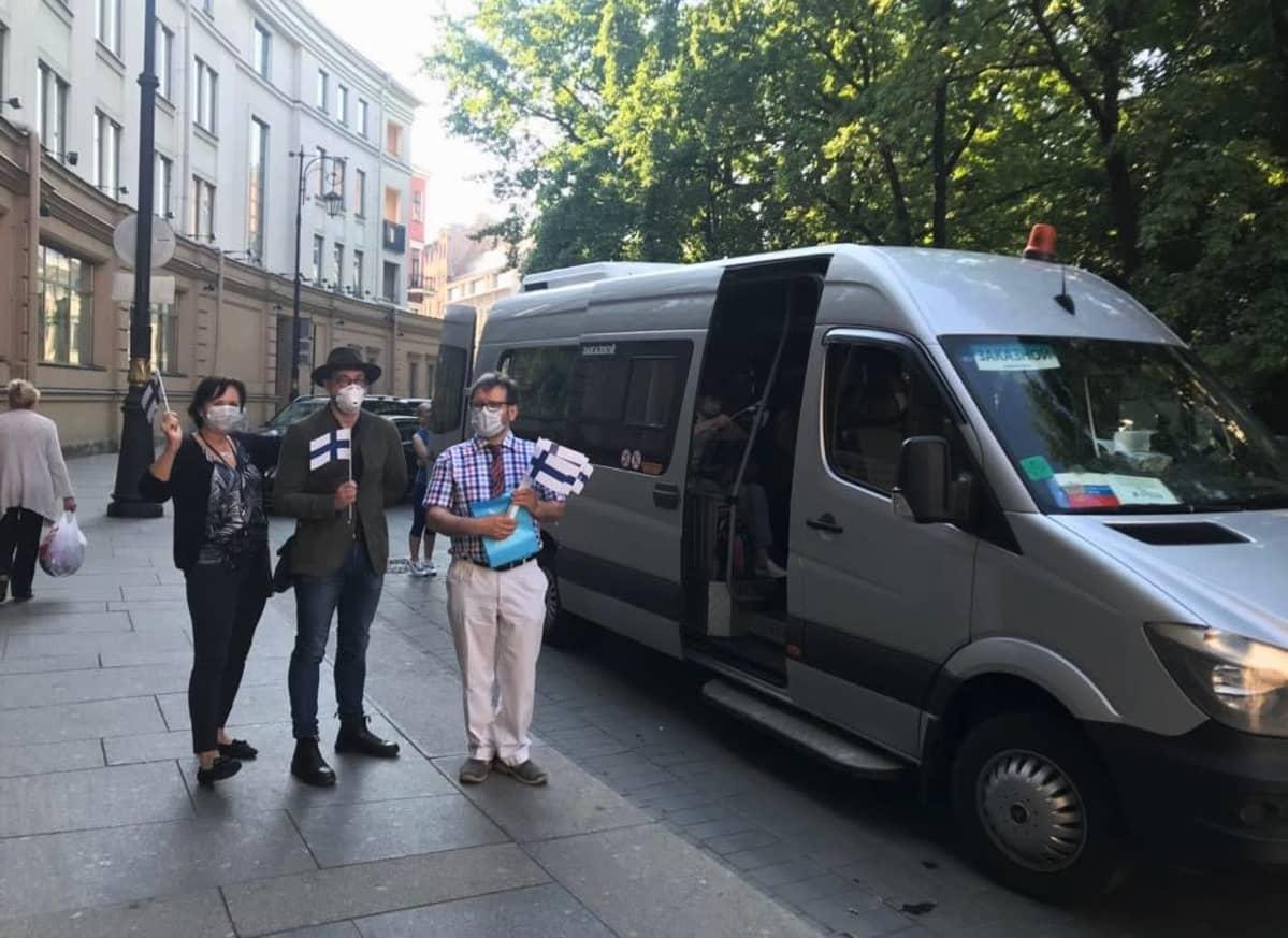 Konsulaatin väki pikkubussin edustalla
