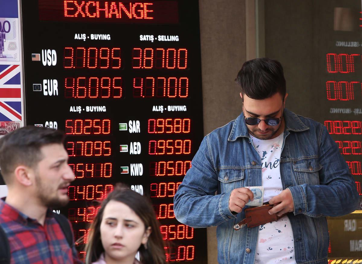 Ihmisiä valuutanvaihtopisteen edustalla istanbulissa