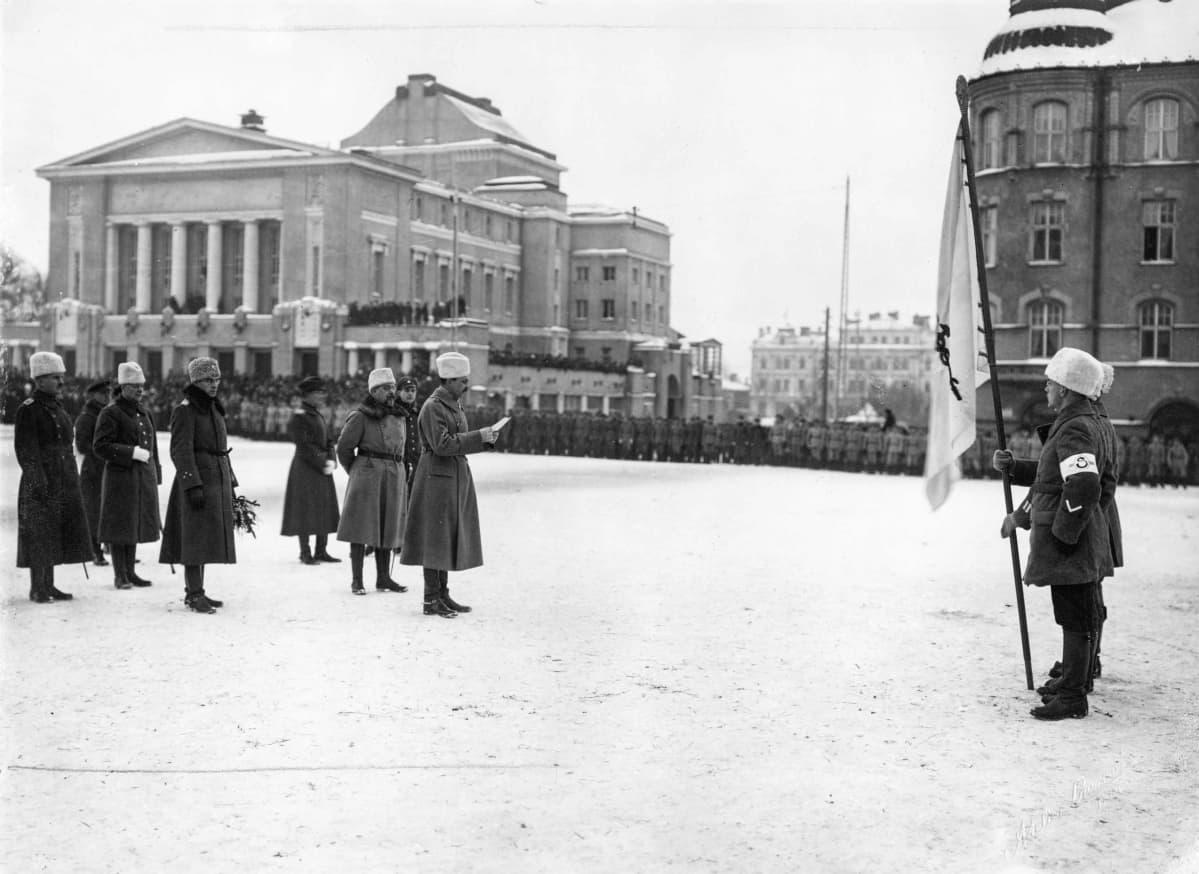 Miehet seisovat torilla sodan alkamisen muistokatselmuksessa.