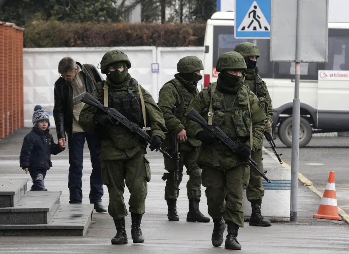 Neljä sotilasta kulkee kadulla vihreissä maastoasuissa, kypärät päässään, kasvot peitettyinä. Miehillä on rynnäkkökiväärit. Taustalla näkyy silmälasipäinen siviiilimies, joka taluttaa pipopäisä pikkupoikaa ja on juuri kumartuneena tämän puoleen kuin selittääkseen jotain.