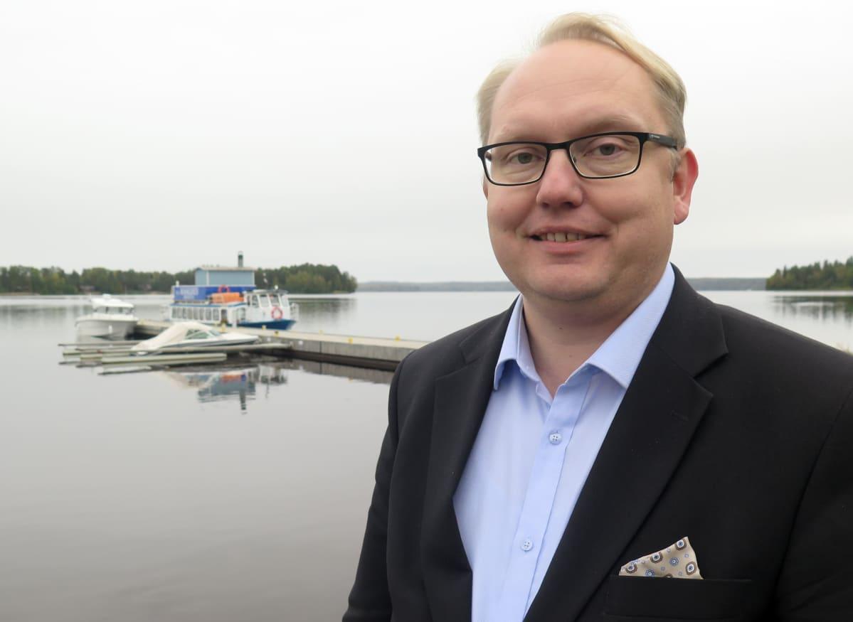Kaupunginjohtaja Kari Tolonen seisoo järven rannalla ja hymyilee.