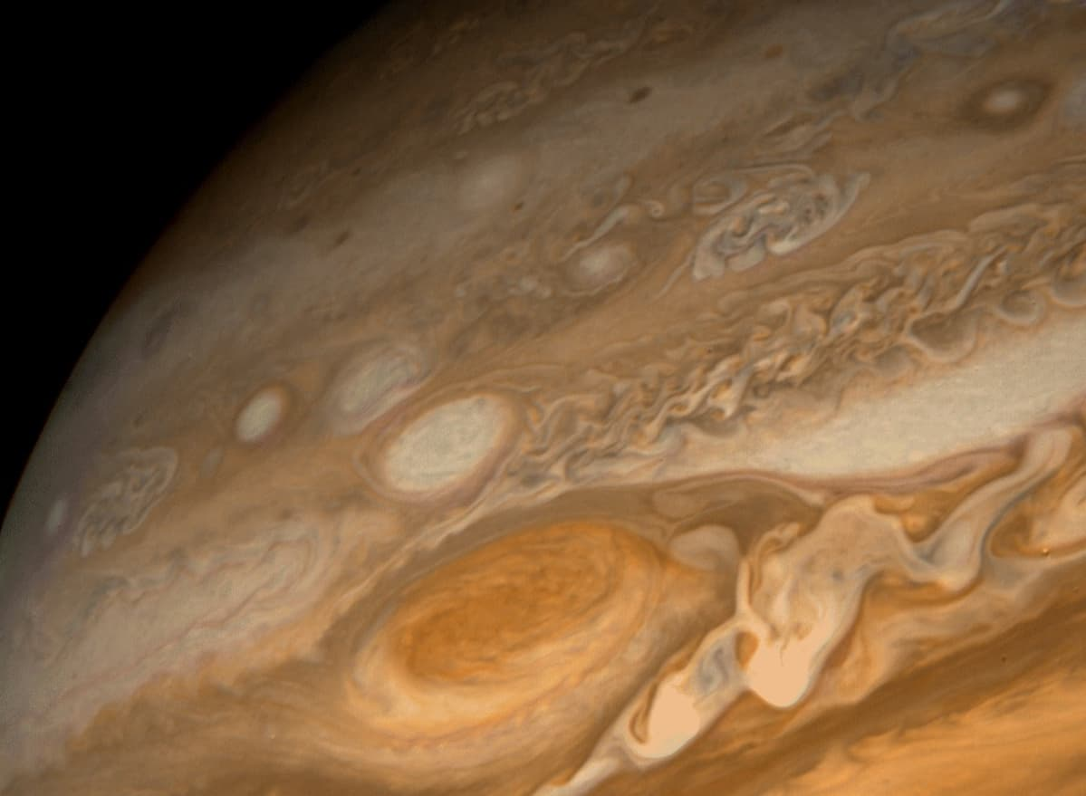 Jupiterin kirjavaa pintaa, jossa yksi kohta näkyy korkeampana ja punaisempana