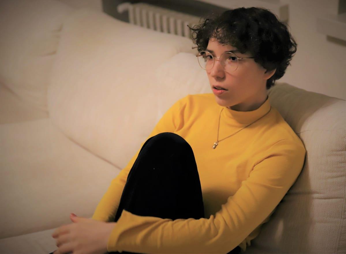 Alva Fontell istuu sohvalla.