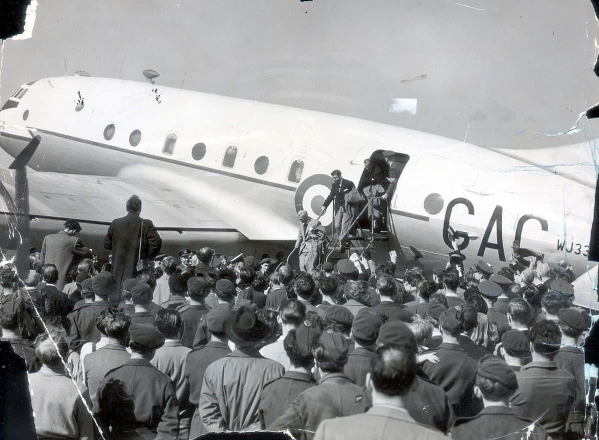 Miehiä laskeutumassa koneesta kentälle, jossa runsaasti vastaanottajia.