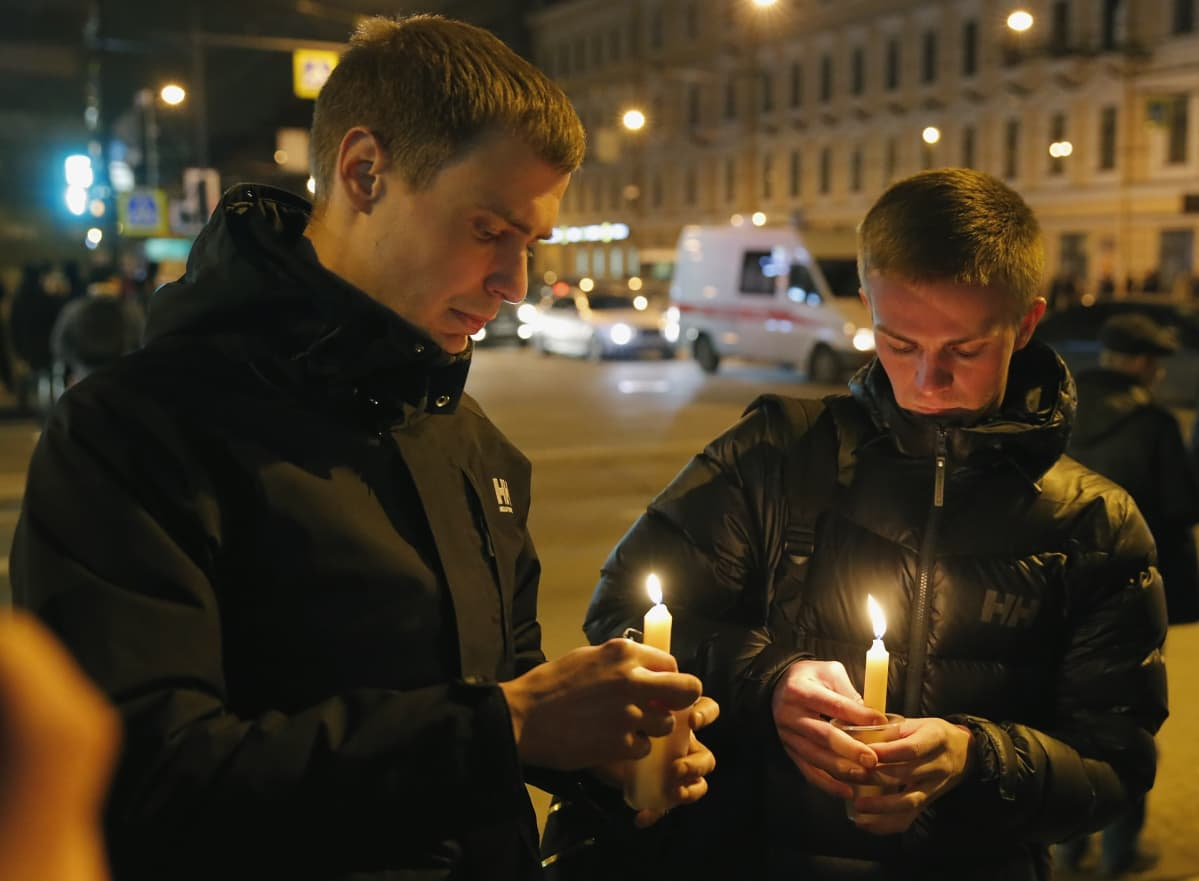 Kaksi nuorta miestä sytyttää kynttilöitä.