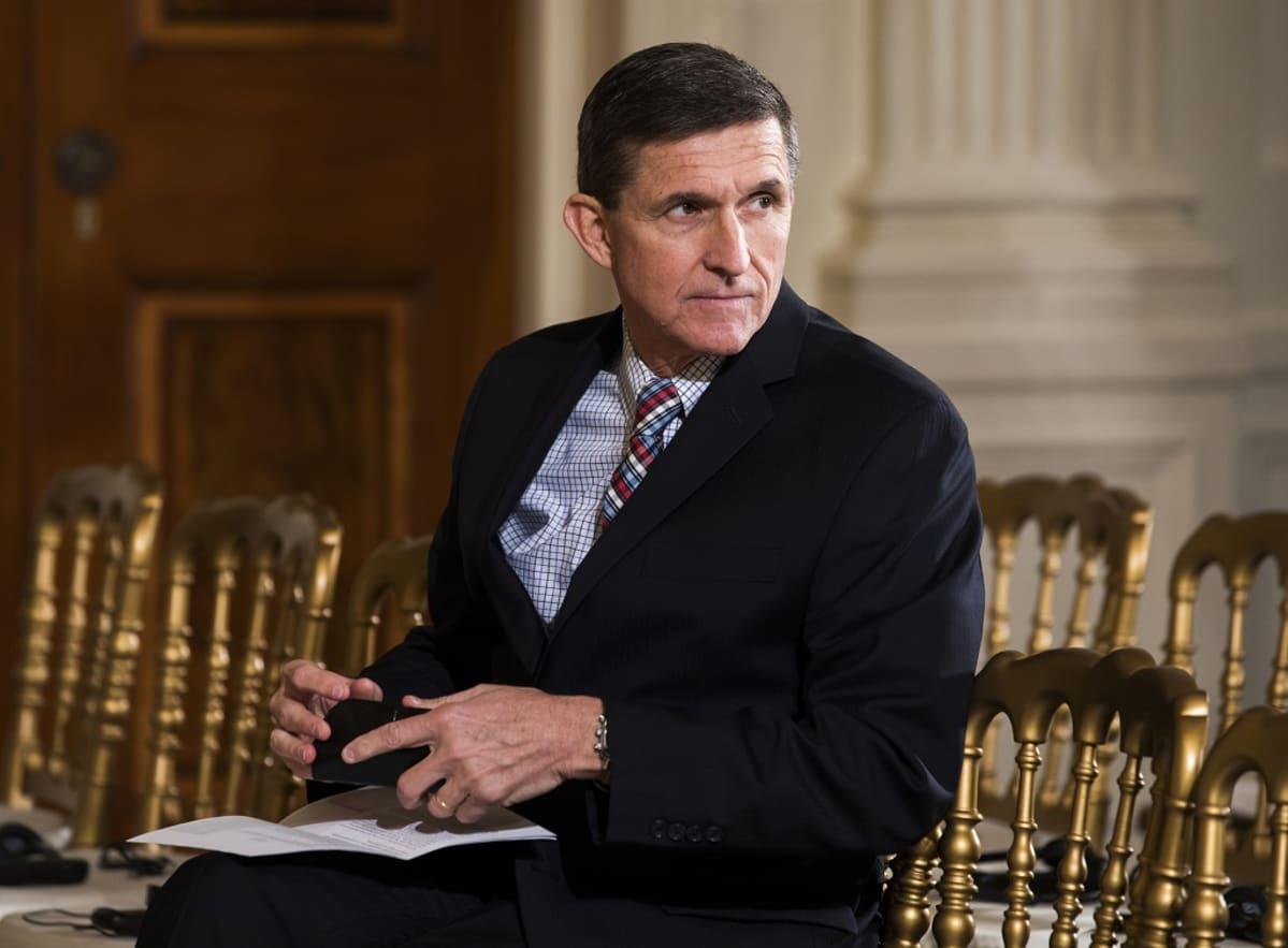 Michael Flynn istuu tuolilla ja katsoo oikealle. Hänellä on tumma puku, vaaleansininen kauluspaita ja monivärinen kravatti.