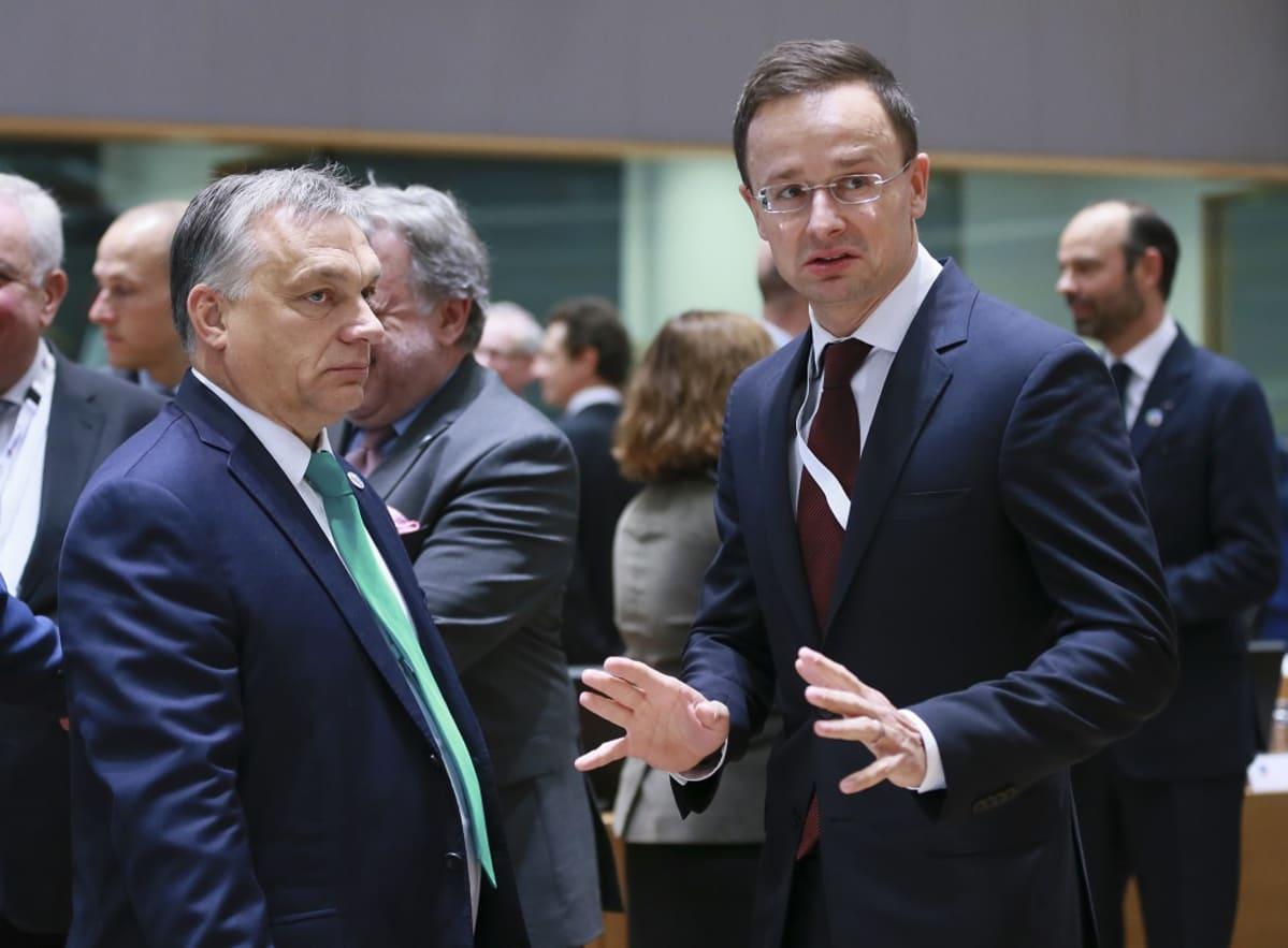 Kuvassa Unkarin pääministeri Viktor Orbán ja ulkoministeri Péter Szijjártó. He seisovat ja taustalla näkyy muita ihmisiä.