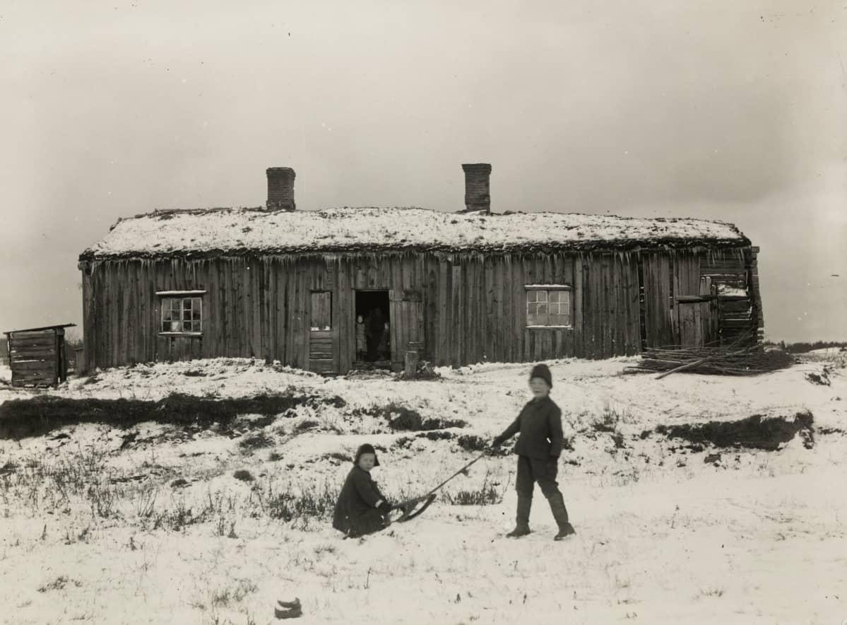 Vanha puinen rakennus, joka on rakennettu 1700-luvulla.  Kuvan etualalla poika vetää toista poikaa kelkalla.
