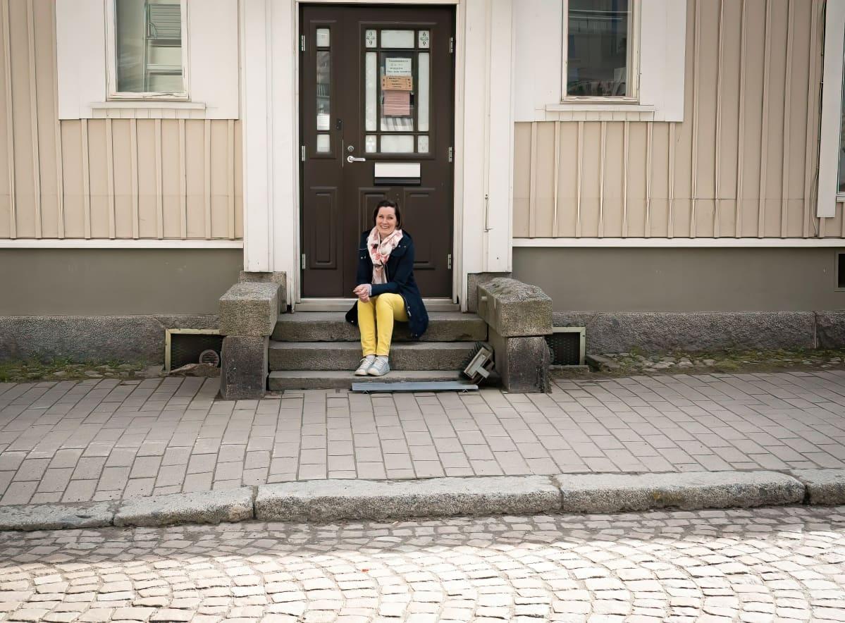 Kakkumestari Jenni Höijer istuu kahvilansa rappusilla.