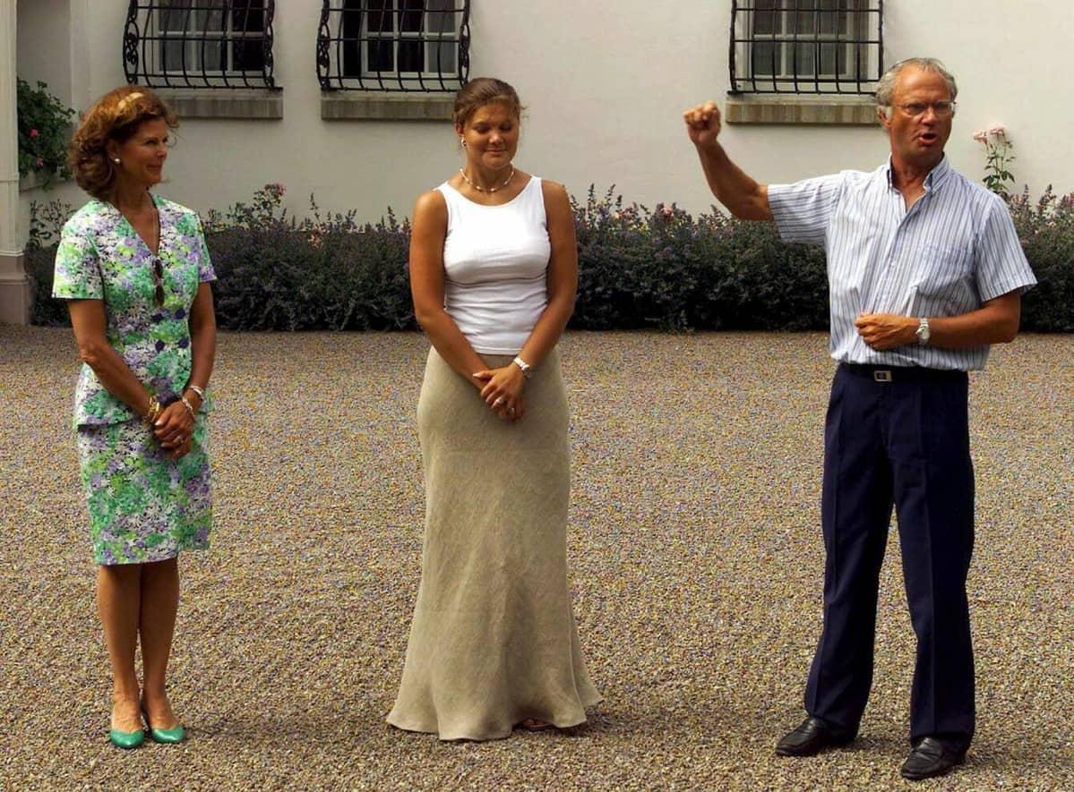 Silviä, Victoria ja Kaarle Kustaa seisovat palatsin pihalla.