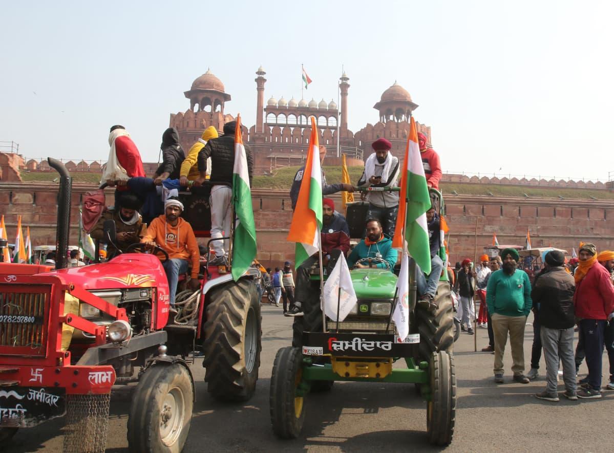Kaksi trakotria on etualalla, punainen ja vihreä. Kuskin lisäksi molempien kyydissä on useita ihmisiä, ja traktorit on koristeltu Intian lipuilla. Taustalla näkyy Delhin Punainen linnoitus.