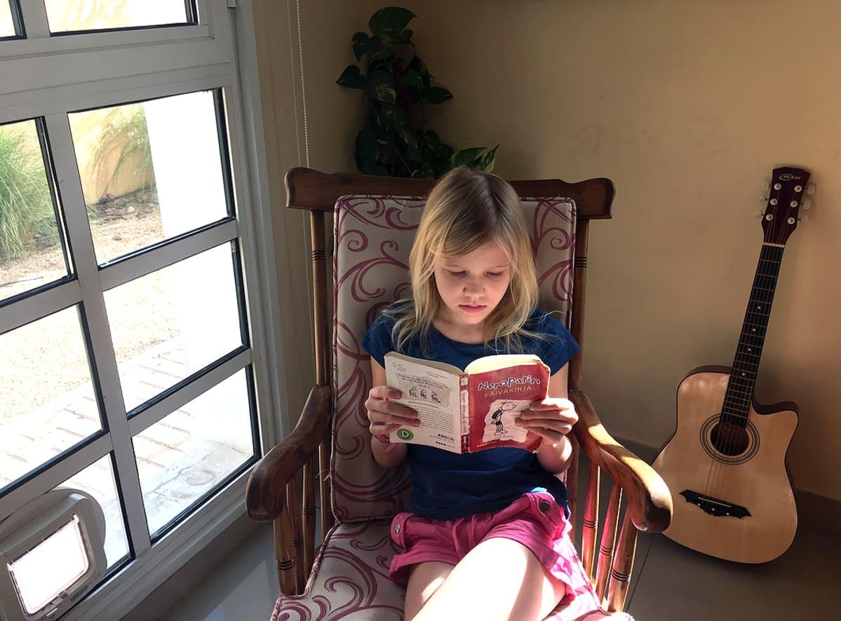 Kuvassa tyttö lukee kirjaa keinutuolissa.