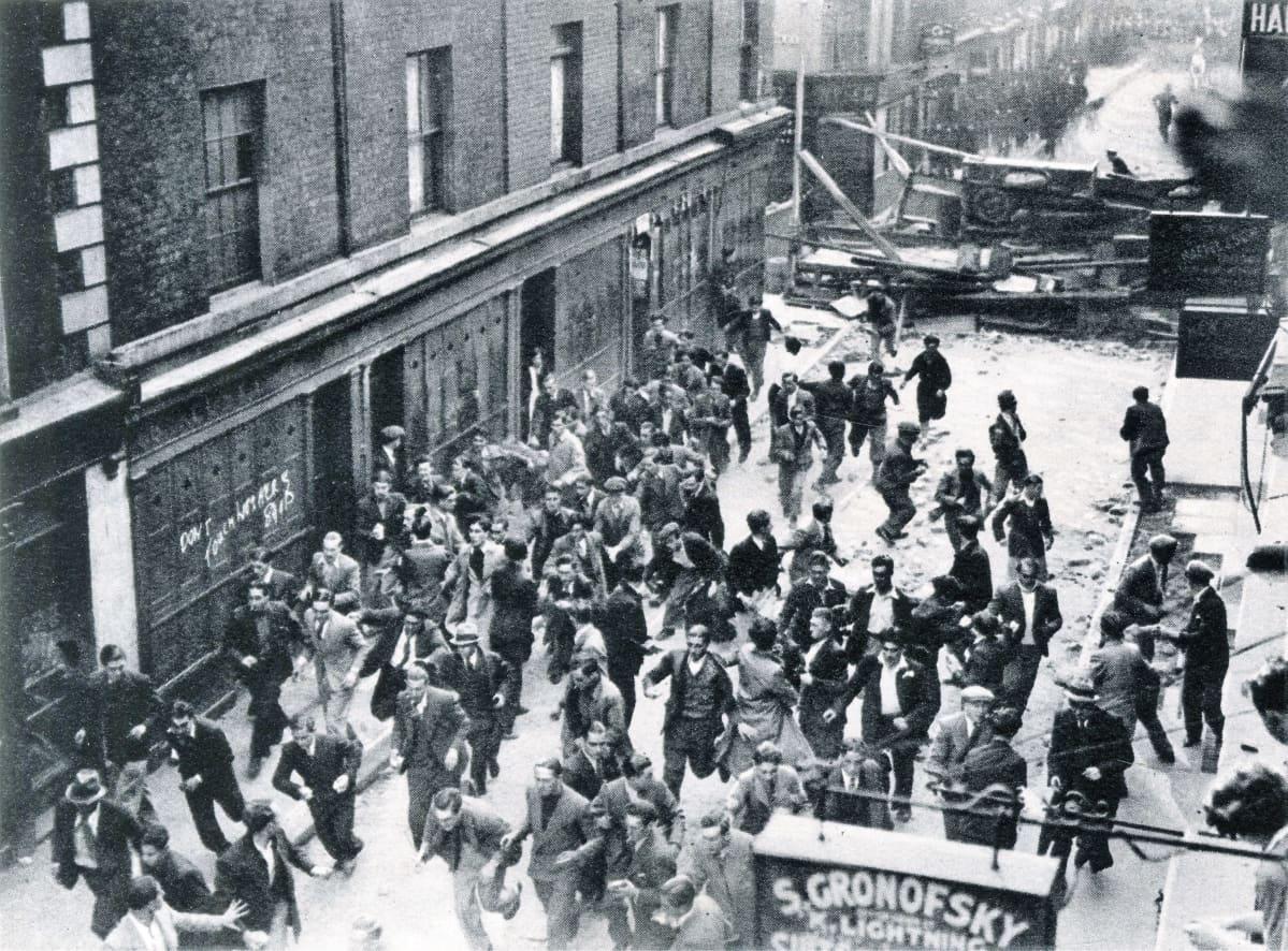 Mustavalkoisessa valokuvassa väkijoukko hajaantuu kadulla. Taustalla näkyy barrikadi.