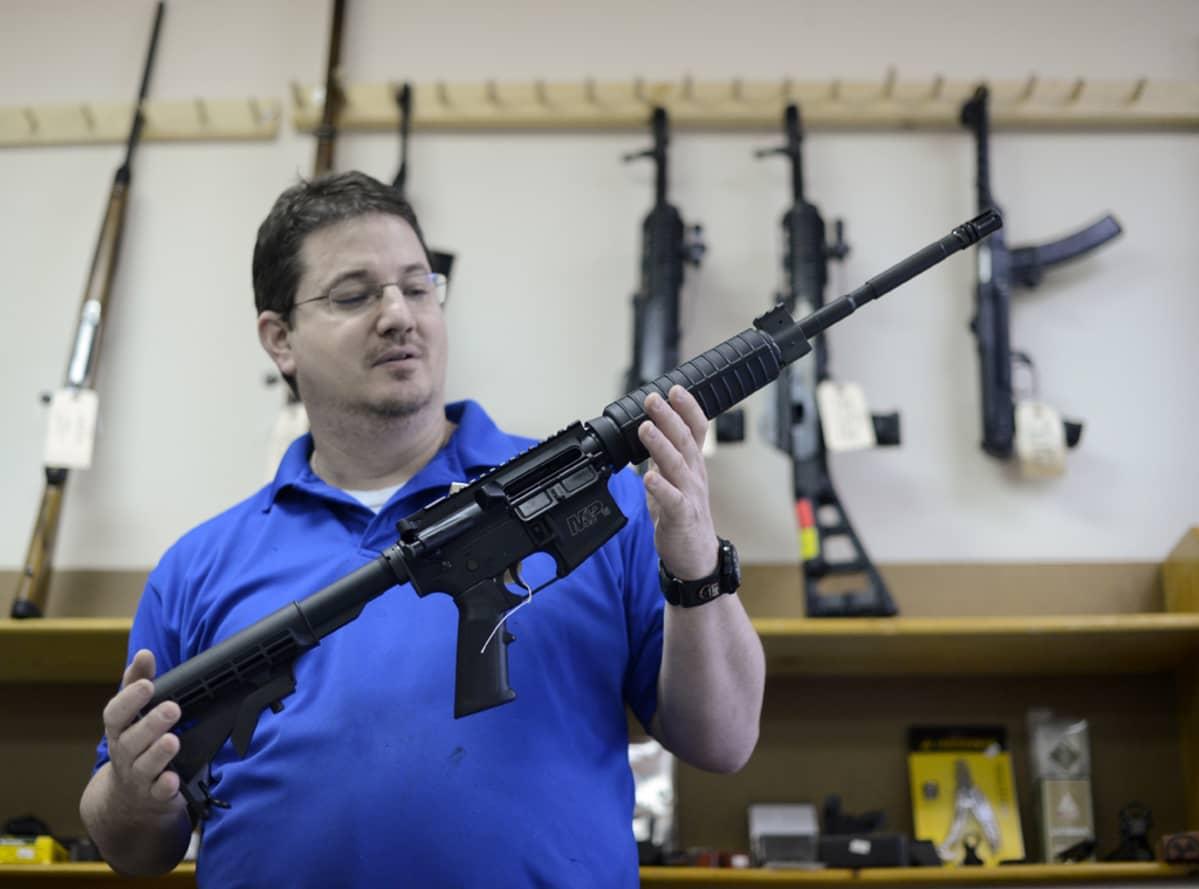 Ron Moon esittelee Smith & Wesson MP15 puoliautomaattista kivääriä omistamassaan asemyymälässä Yhdysvalloissa.